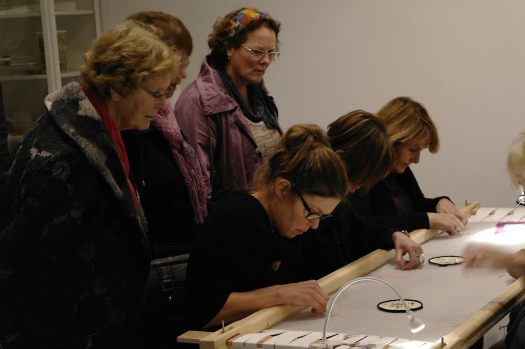 Bezoekers museum kijken toe hoe deelnemers werken