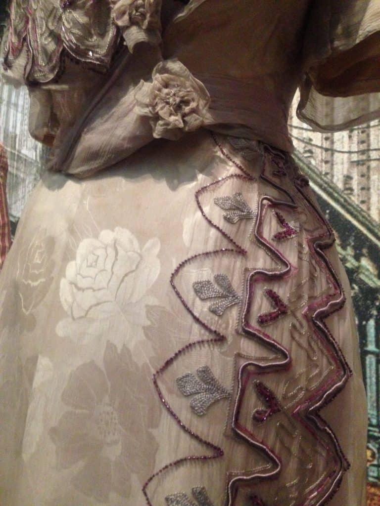 Detail rok taupe-kleurige japon met kralenborduursel