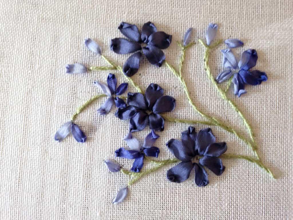Blauwe bloemen in zijdelint. Zie je het verloop van kleur in het lint?