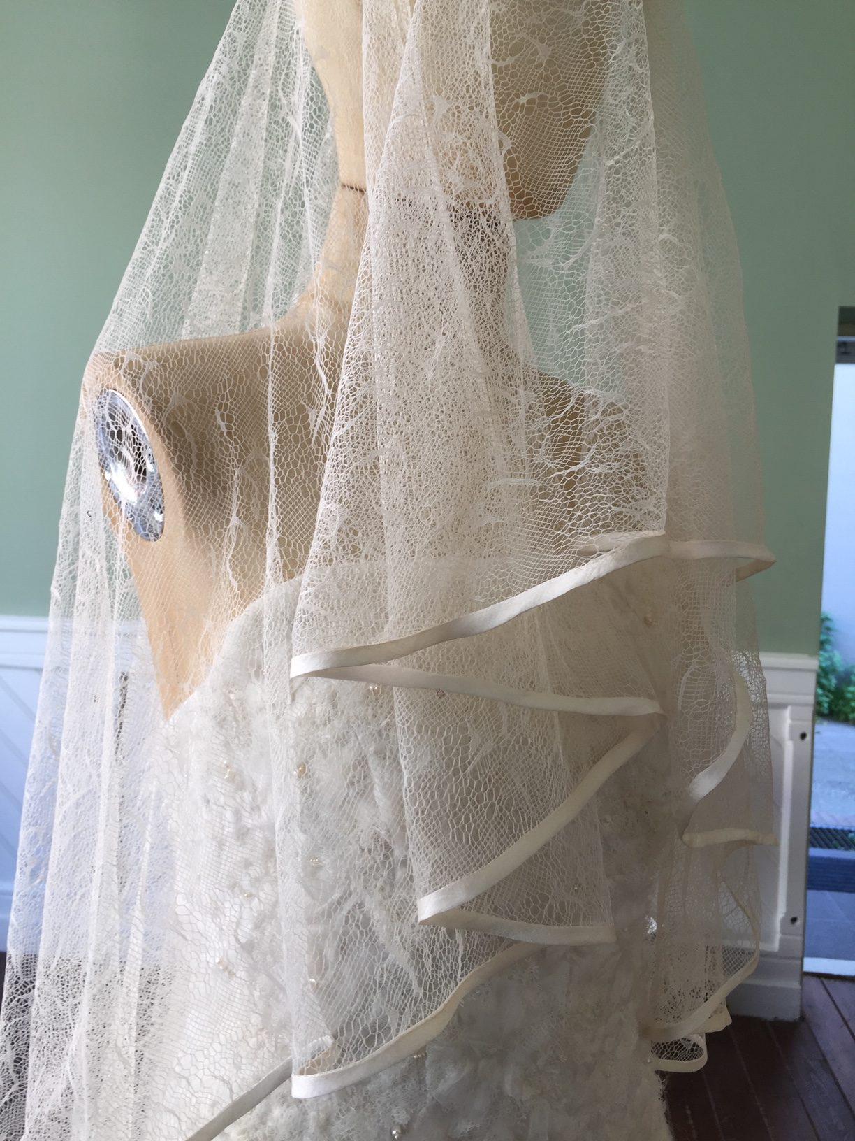 Bruidssluier van tulle met zijden afwerking.